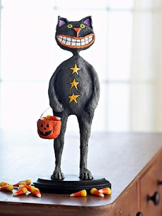 With his toothy grin and a pumpkin bucket, this cool cat is ready for a night of trick-or-treating! Reminiscent of vintage figures, ours is fashioned from plastic foam, dowels, and painted papier-mache