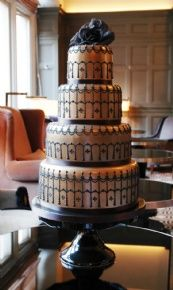 This cake was inspired by glamourous bronze silk corsets with black lace detailing. The chocolate tiers are lustred with bronze before the intricate black pearl designs is added.