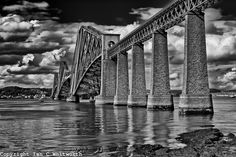 A black and white view of the Firth of Forth Bridge in Scotland.