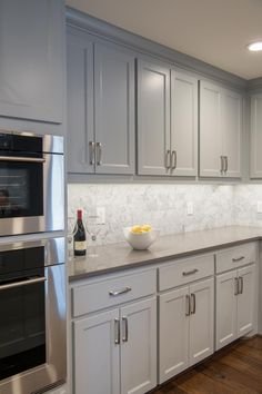 Carrara marble makes for a pretty backsplash in contrast to this kitchen's gray cabinets. The countertops are quartz.