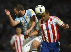 Paraguay's defender Paulo Da Silva (R) heads the ball next to Argentina's Gonzalo Higuain during their Russia 2018 World Cup football qualifier match in Cordoba, Argentina, on October 11, 2016. / AFP / EITAN ABRAMOVICH