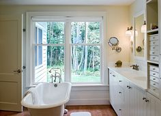 Farmhouse style bathroom with a clawfoot bathtub - timber floor, vanity, shaving mirror.