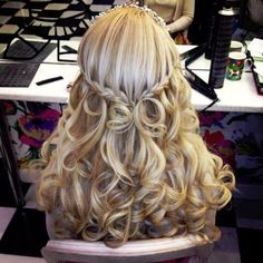 Braided in the back, half up into voluminous princess curls with a ...