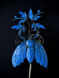 Blue kingfisher feathers adorn this antique hairpin.