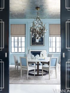 A jewel box of a dining room is splashed in robin's egg lacquer and glitters with a silver foil ceiling. A strongly sculptural table and crisply tailored neoclassical chairs bring it all down to earth.   - Veranda.com