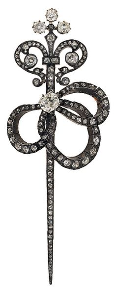 diamond brooch - Designed as a sword with scrolling top and flexible bow tassel, the old cushion-cut diamond centre to a cushion and old brilliant-cut diamond surround, mounted in silver and gold, circa 1880.