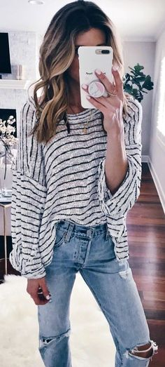 Woman wearing gray sweater and denim jeans holding white smartphone.   SpringOutfits  SpringDress   56489393bfb