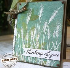 "Patterned paper background. Stamp ""Silhouette Grass"" by Hero Arts with VersaMark & emboss in white. Sponge corners with tea dye distress ink. Add embellishments and sentiment."