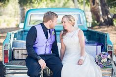WEDDINGS – norrisphoto #norrisphoto - Country styled wedding with bride and groom sitting on the back of a pickup truck. While she wears a classic white gown, he wears a light purple vest and tie over all black. Her wedding bouquet made up of purple and white flowers ties it all together. Los Angeles wedding photographer does a great job capturing the happiness of the newlyweds. #countrywedding #purpleweddingcolors #weddingphotographerlosangeles