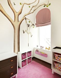 Adorable pink girl's nursery features walls painted with a monkey in a tree mural lined with a two-tone dresser next to an open shelving unit filled with pink woven baskets atop a pink rug beside an arched window dressed in a pink geometric roman shade above a pink lacquer bookshelf mounted on wall.