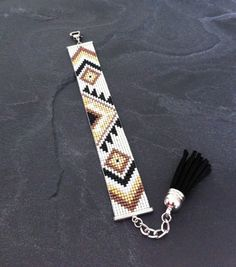 Bracelet Manchette Tribal Noir Marron Or blanc et argenté par TDFTheDreamFactory, I love the tassel at the end Loom Bracelet Patterns, Seed Bead Patterns, Bead Loom Bracelets, Beading Patterns, Jewelry Patterns, Bead Jewellery, Seed Bead Jewelry, Beaded Jewelry, Seed Beads