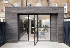 Brickwork, terrazzo surfaces and green-hued furnishings add character to this London townhouse, which has been renovated and extended by HÛT.