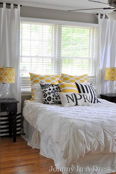 gray walls & white bedding -- adding the black & yellow accents with pillows and lamps.