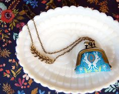 dancing rabbits folklore style tiny coin purse necklace- leaf branch charm detail
