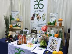 Arbonne product display at a vendor show. Artificial flowers, grass and fruit…