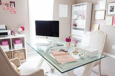 Drenched in sunlight, this home office is the perfect working space for any modern woman. Plush nude-colored chairs surround a glass top working table. The neutral hue extends to the walls, setting an ultra-calm and distraction free mood for the space. To add some character and color, the office is decorated in gold and pink : with golden tassels and …
