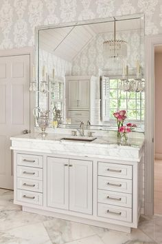 Exquisite bathroom boasts a light gray washstand topped with thick marble fitted with a hammered metal sink and sleek gooseneck faucet under a large square beveled mirror alongside a marble floor laid out in a diamond pattern.
