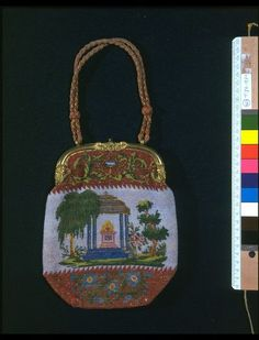 Great Britain, possibly France, ca. 1840. Canvas bag entirely covered in glass beads. Oval shaped, the beadwork divided into three horizontal sections; the top and bottom sections beaded with a red background and floral motifs in green, blue, red, yellow & gold. The larger middle area contains a scene depicting 2 large trees surrounding a blue architectural monument containing a flaming altar against a white background. It has an ornate gilt metal clasp & a handle of multicolored, braided…