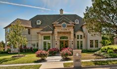 Absolutely stunning stucco home with stone accents and mature lush landscaping.