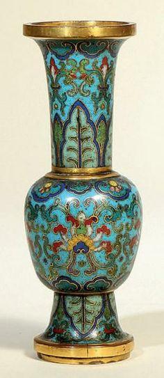 CHINE  Epoque QIANLONG (1736 - 1795) Petit vase de forme «gu» en bronze doré et émaux cloisonnés à décor de fleurs de lotus stylisés dans leur feuillage sur fond bleu turquoise, le col orné de frises de bananiers, l'épaulement et le col orné d'une frise de lingzhi. H.: 13,5 cm.