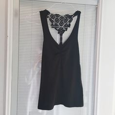 Black Tank Black tank top with crochet back detailing. Racetrack with slight bunching on front to accentuate the neckline. Great every day black tank top. Tops Tank Tops