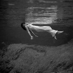 Underwater view of a woman floating in water Art Print by Marquis De Noir
