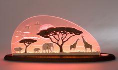 Die Weigla Motivleuchte Safari ist ein elegantes Wohnaccessoire aus hochwertigem Plexiglas und Eschenholz