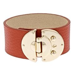 Orange leather cuff bracelet with oversized buckle closure.  Product: CuffConstruction Material: Leather, zinc, ...
