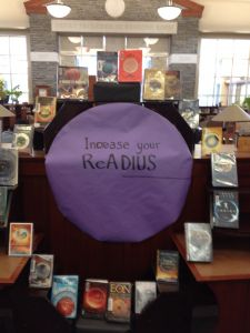 Increase your ReADIUS. Library display of books with circles on the cover.