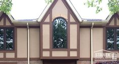 Custom-shaped eyebrow window perfectly suits this Tudor-style home. #homeimprovement #homedesign