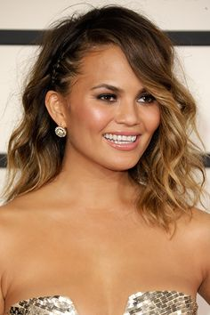 A tight braid at the hairline tucked behind one ear makes side-parted beach waves seem more dramatic.
