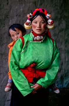 Asia | Portrait of a woman wearing traditional clothes, headdress and beaded silver jewelry, carrying her child at a Horse Festival in Tagong, Kham, Tibet | © Steve McCurry #beads # babywearing