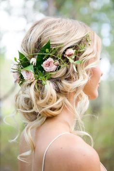 Bride with beautiful wedding hair, low, loose curls and a flower hairpiece