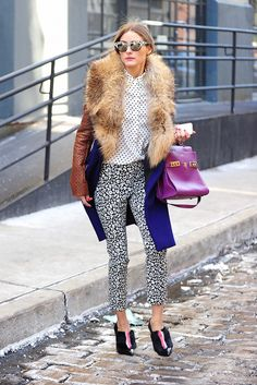 Olivia Palermo in polka dot button blouse, fur collared coat, black and white leopard pants, purple bag, and cat-eye sunglasses