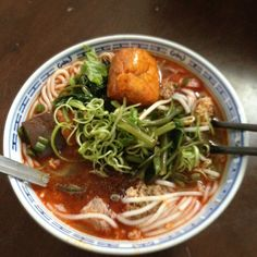 Bun Rieu a traditional Vietnamese noodle dish. Tomato and shrimp based broth, crab patties, deep fried tofu puffs, split water spinach stems and shrimp paste.