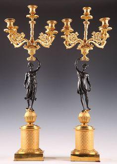 Une paire de candélabres à cinq feux avec deux personnages en bronze à patine brune vêtus de drapées aériens attachés sous la poitrine, en position de marche sur de nuées stylisées, tenant de leur bras gauche une vase d'où jaillissent les cinq bras de lumière en bronze doré richement décorés de rinceaux fleuris, de feuillages tournés en volute et de cannelures et terminés par de bobèches feuillagées. Ils reposent sur une sphère en bronze doré agrémentée de longues feuilles lancéolées, posée…
