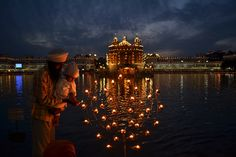 A Sikh father helps his son to light a lamp, near the illuminated Golden Temple, the Sikhs' holiest shrine, on the festival of Baisakhi in Amritsar, Punjab, India, Monday, April 14, 2014. Baisakhi, which marks the Sikh New Year's Day, is also a harvest festival.