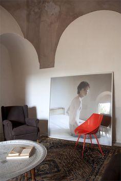 Un altro living in cui ecletticamente convivono una poltrona di modernariato e una sedia Lago di Starck. L'opera fotografica è di Massimo Simeone