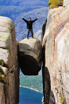 A man posing for a photo on top of the Kjeragbolten, a huge boulder gripped between two cliffs in Norway