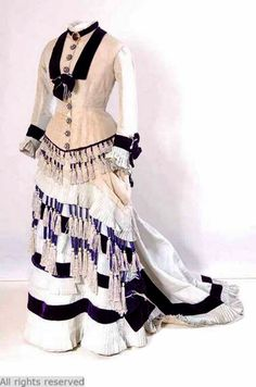 Day dress, Dutch, ca. 1875-80. Bodice and skirt in light blue grosgrain silk, decorated with fringe with tassels in purple and light blue chenille cord; lined body in off-white cotton; lap premises in yellow cotton sateen; fitted to hip, collar, long curved sleeves, lingering close asymmetrically draped skirt with queue. Mode Museum, Antwerp