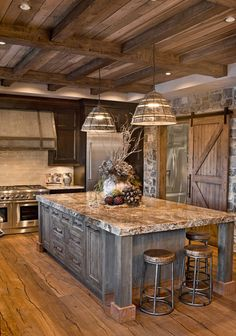 Rustic kitchen oversized island; custom cabinetry; kitchen cabinets; distressed; rustic; glazed; knotty alder; stained; metal accents; inset doors;