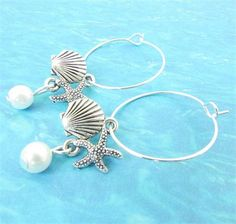 These shell hoop earrings are the perfect beach lover gift. A sweet shell charm with a starfish and a white pearl add ocean inspiration to these dangle earrings. Do you need bridesmaids gifts? These can be purchased in sets for your beach wedding. These can also be customized as a wine charm gift set with different pearl colors. These beach wine charms work with any long stem glass.