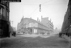 Lindsay Street and Overgate, Dundee.  This photograph shows the intersection of Lindsay Street and Overgate.  The corner building is John Burnett  Sons, family bakers, at No. 119 Overgate. Next door was A. Lamb, stationer, and then John S. McGregor, the furniture dealer.   To the right of the prominent tower of the Lindsay Street Works is Dundee's Court House, in Bell Street.