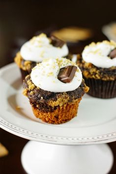 Smores Cupcakes ~ graham cracker and chocolate batters layered together, sprinkled with brown sugar-graham crumbs, and topped with homemade marshmallow cream frosting.   www.thekitchenismyplayground.com
