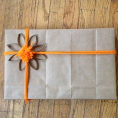 Present wrapped in brown paper bag tied with yarn.