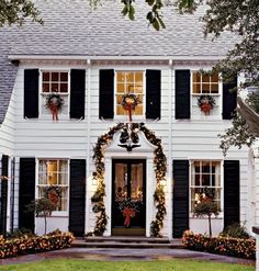 Christmas wreaths on the windows, garland around the door, and lights on the shrubs - beautiful...