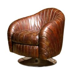 Wood-framed accent chair with textured leather upholstery and an exposed pedestal base.      Product: ChairConstruction Ma...