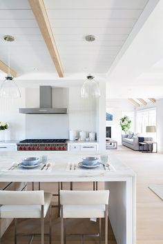 All-white kitchen with exposed wooden beams, a marble bar, glass pendant lights, and mosaic backsplash