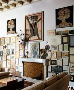 Three multimedia works by Enrico Baj hang high on a living room wall in the late Artist's villa in Vergiate, Italy. Fireplace screen covered in vintage flame stitch fabric | archdigest.com