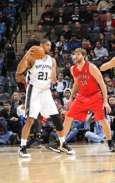 SAN ANTONIO, TX - DECEMBER 26: Tim Duncan #21 of the San Antonio Spurs protects the ball from Aaron Gray #34 of the Toronto Raptors during the game between the Toronto Raptors and the San Antonio Spurs on December 26, 2012 at the AT Center in San Antonio, Texas